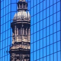 Reflection of the cathedral bell tower in a modern building at Santiago