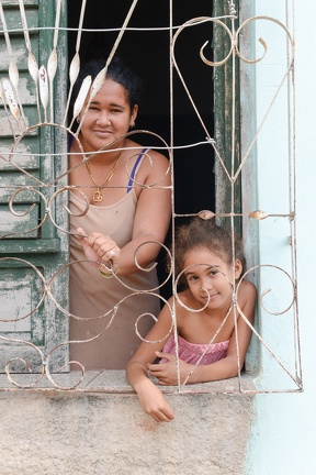 Mom with her daughter at the window in the colonial town of Trinidad