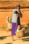 Woman with her son on a basket at the archaeological site of Bagan