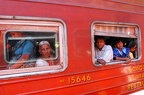 People who look out of the windows of the train that is carrying them to Kandy